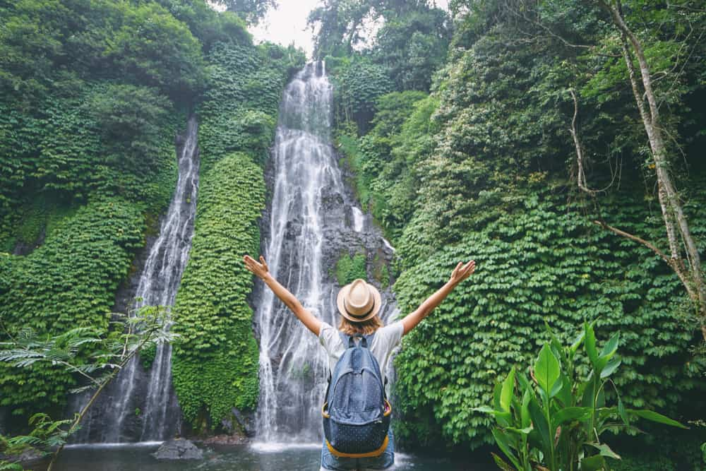 Person standing in front of Bali waterfalls